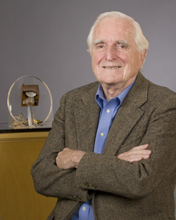 Portrait of Doug Engelbart with the original mouse in near background