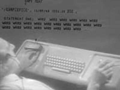 stillshot of Doug demonstrating mouse and keyset during 1968 demo